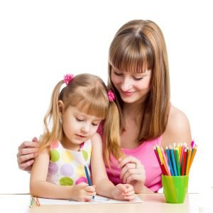 Developmental, Learning and Behavioural Disorders in Children and Adolescents: A woman is assisting a child draw and color