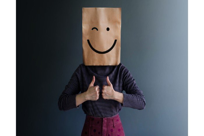 well-being: a woman wearing a brown bag with a smiley on it