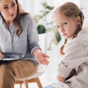 CHC40313 Certificate IV in Child, Youth and Family Intervention: A lady is trying to talk to a child who seems hesitant