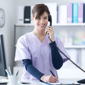 medical reception skills: girl in a scrub suit is answering the phone