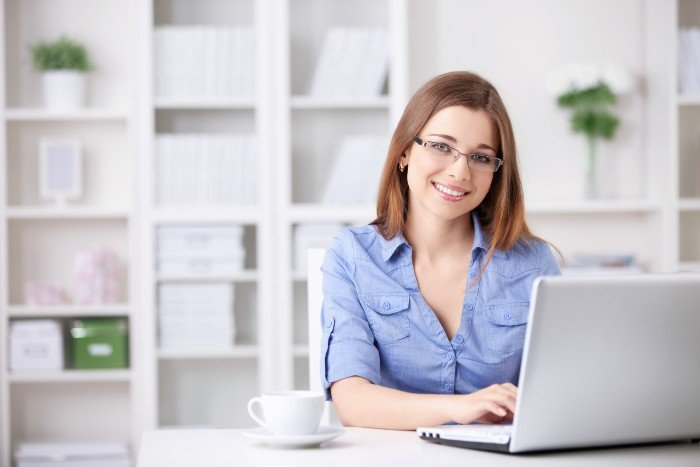 returning to work: woman smiling as she looks up from her laptop