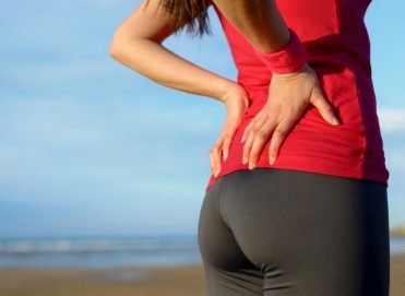 back pains: girl is standing up with her hands on her lower back area